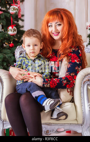 Happy mother and her little child surrounded with Christmas decorations - Stock Photo