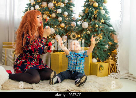 Happy mother and her little child surrounded with Christmas decorations. Kid is playing with bubbles - Stock Photo