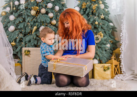 Happy mother and her little child surrounded with Christmas decorations. Opening presents - Stock Photo