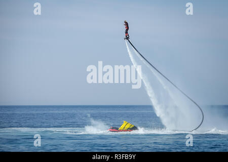 Dugi Rat, Croatia - October 20, 2018: A man is doing acrobatics with flyboard attached to jet ski close to the shore in Dugi Rat, Croatia. - Stock Photo