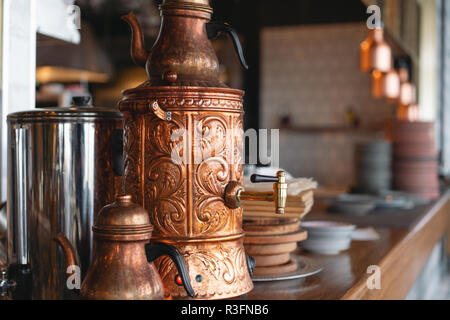 Turkish copper teapot. Drinking traditional Turkish Tea with kettle in cafe - Stock Photo