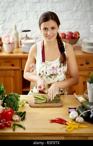 beautiful young woman, brunette slicing asparagus in the kitchen at a table full of organic vegetables - Stock Photo