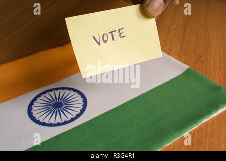 Voting concept - Person holding Hand Written Voting Sticker on India Flag. - Stock Photo
