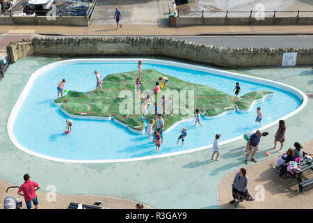 View looking out over Ventnor Map Paddling Pool on a hot summers day while young children / kids paddle and play in the water. Isle of Wight. UK (98) - Stock Photo