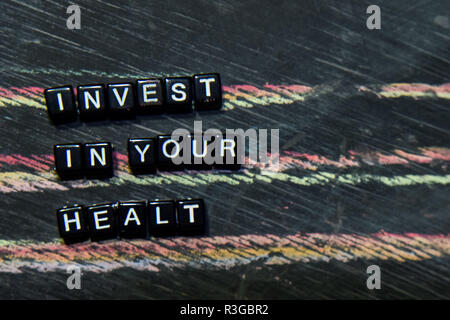 Invest in Your Health on wooden blocks. Cross processed image with blackboard background. Inspiration, education and motivation concepts - Stock Photo