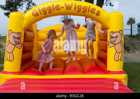 Three children age 4, six, eight years old, playing / bouncing safely on an inflatable bouncy castle in a café / pub / restaurant garden. (98) - Stock Photo