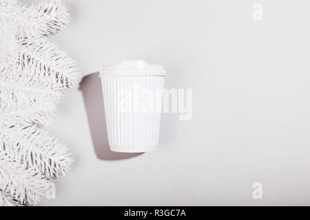White cup of coffee to go with branch of Christmas fir tree on grey background. Flat lay style. Place for text. - Stock Photo