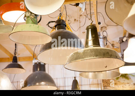 a group of vintage metal lightshades hanging together - Stock Photo