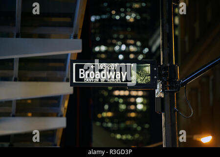 (selective focus) Broadway sign illuminated at night in Manhattan, New York. Blurred building on background. - Stock Photo