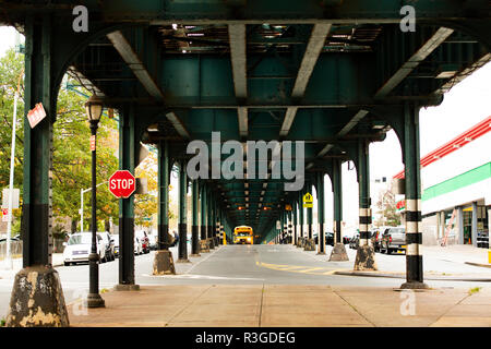 A school bus is passing under the railway bridge in the Bronx, New York city, USA. - Stock Photo