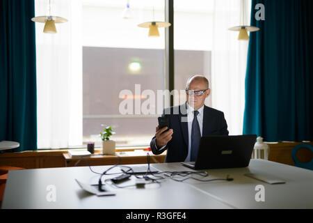 Senior Businessman Using Phone And Laptop At Work - Stock Photo