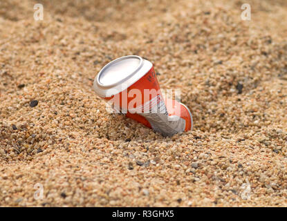 environmental problem - aluminium drink container in sand on seacoast at the sea - Stock Photo