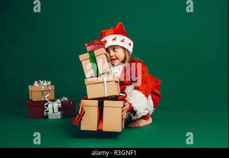 Little girl in santa claus dress lifting a pile of gift boxes. Kid in santa costume playing with gift boxes. - Stock Photo