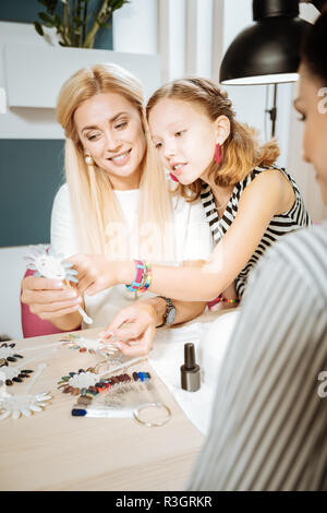Daughter wearing pink earrings helping her mother in choosing nail color - Stock Photo