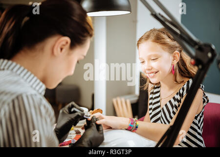 Cute beaming teenage girl feeling excited coming to manicure saloon - Stock Photo