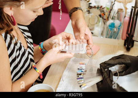 Cute stylish teenage girl feeling excited choosing color for her nails - Stock Photo