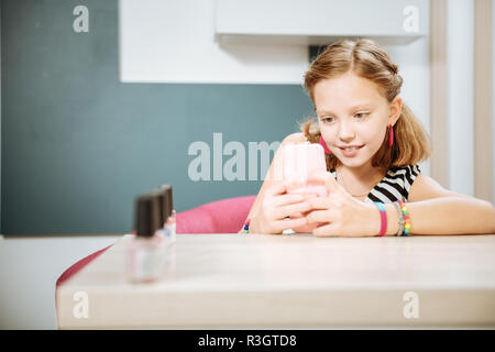 Modern teenage girl making photo of colors of nail polish - Stock Photo