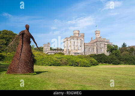 Wicker woman statue and castle in Stornoway, United Kingdom. Willow sculpture on green grounds of Lews Castle estate. Architecture and design. Landmar - Stock Photo