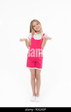 Girl in hot pink jumpsuit isolated on white background. Smiling kid wearing summer outfit. Child with hands in I don't know gesture. Blond girl with l - Stock Photo