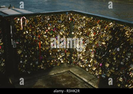 Romantic padlocks placed on bridges by couples of lovers in love who chain their destinies - Stock Photo