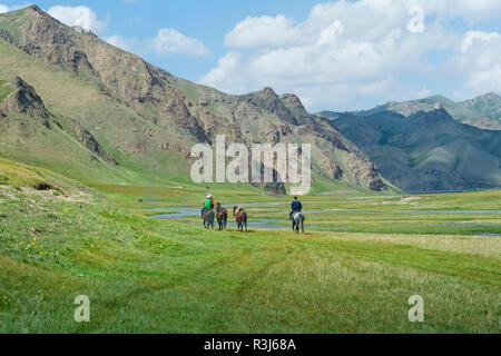 Horsemen riding in Kurumduk valley, Naryn province, Kyrgyzstan - Stock Photo