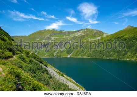 Bergkette mit saftigen Wiesen und einem großem See im idylischen Salzburger Land unter blauen Himmel. - Stock Photo