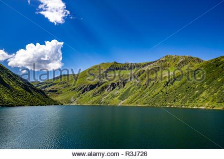 Bergkette mit saftigen Wiesen und einem großem See im idyllischen Salzburger Land unter blauen Himmel. - Stock Photo