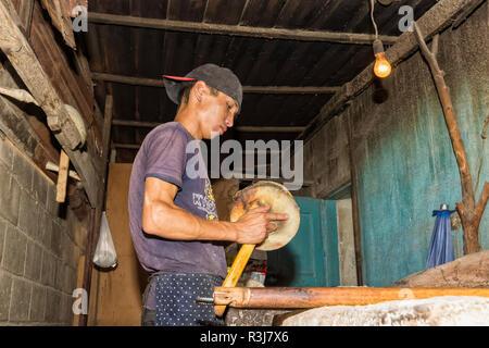 Kyrgyz man preparing the traditional Kyrgyz bread, Kochkor village, Road to Song Kol Lake, Naryn province, Kyrgyzstan - Stock Photo
