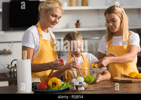 cute happy child with mother and grandmother cooking vegetable salad together in kitchen - Stock Photo