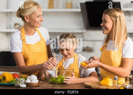 happy three generation family cooking vegetable salad together - Stock Photo