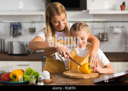 smiling young woman helping little daughter cutting pepper in kitchen - Stock Photo