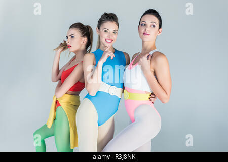 beautiful young spotty women in colorful sportswear posing together isolated on grey - Stock Photo