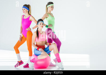 athletic young women in 80s style sportswear posing together on grey - Stock Photo