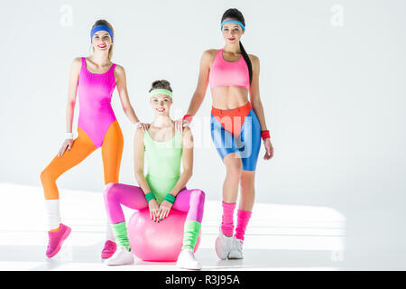 athletic young women in 80s style sportswear smiling at camera on grey - Stock Photo