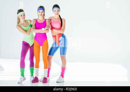 beautiful sporty young women in 80s style sportswear smiling at camera on grey - Stock Photo