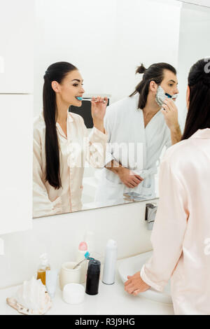 beautiful woman brushing teeth and handsome man shaving in front of mirror in bathroom - Stock Photo