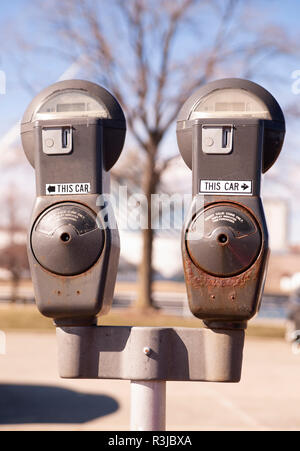 A pole with dual coin operated parking meters stands in winter on the street - Stock Photo