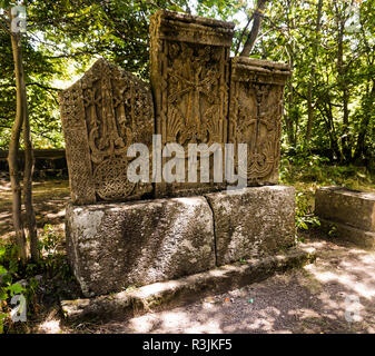 Three Carved Traditional Armenian Stone Crosses on a Rock in a Park - Stock Photo