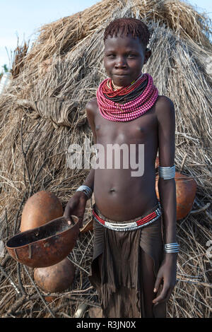 Africa, Ethiopia, Southern Omo Valley, Nyangatom Tribe. A young Nyangton girl with her calabash standing in front of her hut. - Stock Photo
