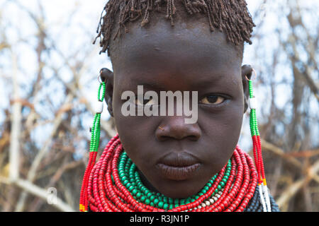 Africa, Ethiopia, Southern Omo Valley, Nyangatom Tribe. Headshots of a young Nyangatom girl wearing bead necklaces. - Stock Photo