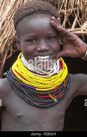 Africa, Ethiopia, Southern Omo Valley, Nyangatom Tribe. A young Nyangatom girl poses in front of her hut with her beaded necklaces. - Stock Photo