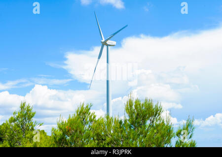 electric generation windmill with blue sky background and green pine below - Stock Photo