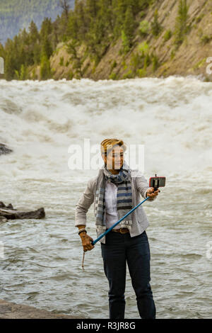 BANFF, AB, CANADA - JUNE 2018: Visitor using a selfie stick to take a selfie picture at the Bow River Falls in Banff. - Stock Photo