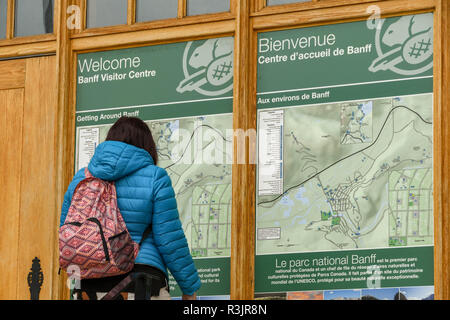 BANFF, AB, CANADA - JUNE 2018: Visitor studying a large map displayed on the front wall of the Banff National Park Visitor Centre in Banff town. - Stock Photo