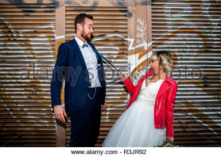 Couple of newlyweds play with suspenders in front of a graffiti metal fence. - Stock Photo