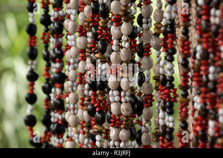 Madagascar, Nosy Be (Big Island) off the northwest coast of mainland Madagascar. Rural roadside handicraft stand selling seed necklaces. - Stock Photo