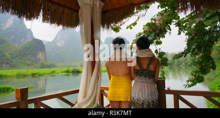 Tourists in spa balcony watching Karst Hills on Mingshi River, Mingshi, Guangxi Province, China - Stock Photo