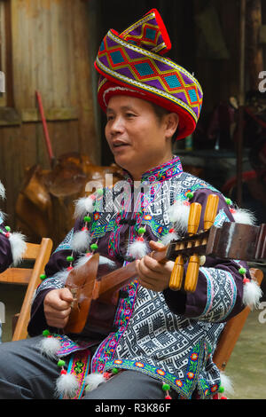 Dong man in traditional clothing playing music, Chengyang, Sanjiang, Guangxi Province, China - Stock Photo
