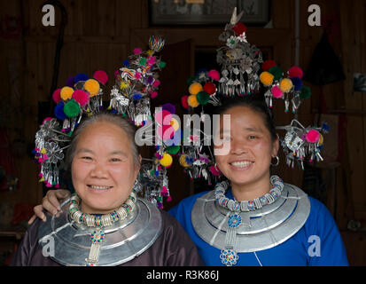 Dong women (mother with daughter) in traditional clothing and jewelry, Chengyang, Sanjiang, Guangxi Province, China - Stock Photo