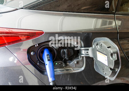 An electric hybrid car is plugged in at home with a blue electric connector. - Stock Photo